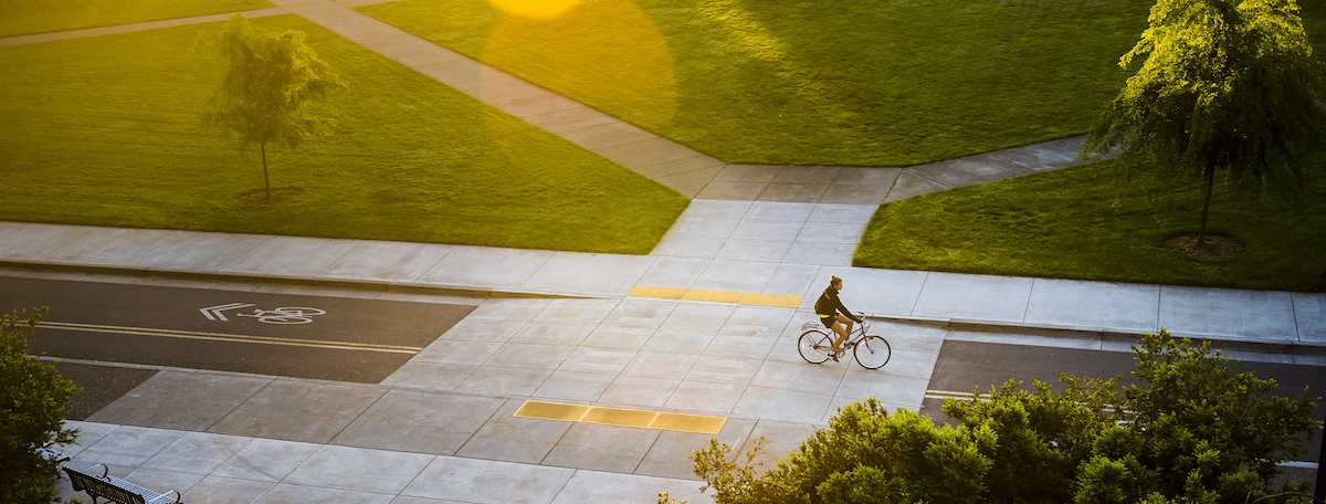 A cyclist travels across campus